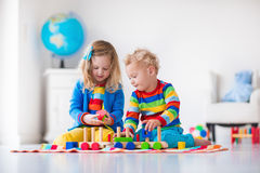 Kids playing with wooden toy train. Children playing with wooden train. Toddler kid and baby play with blocks, trains and cars. Educational toys for preschool Royalty Free Stock Photo