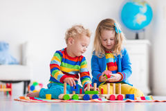 Kids playing with wooden toy train. Children playing with wooden train. Toddler kid and baby play with blocks, trains and cars. Educational toys for preschool Royalty Free Stock Photography