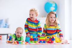 Kids playing with wooden toy train. Children playing with wooden train. Toddler kid and baby play with blocks, trains and cars. Educational toys for preschool Stock Photos