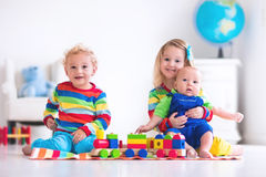 Kids playing with wooden toy train. Children playing with wooden train. Toddler kid and baby play with blocks, trains and cars. Educational toys for preschool Royalty Free Stock Images