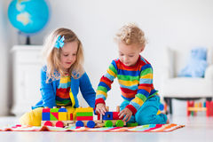 Kids playing with wooden toy train. Children playing with wooden train. Toddler kid and baby play with blocks, trains and cars. Educational toys for preschool Royalty Free Stock Photos