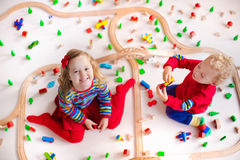 Kids playing with wooden train set Stock Image