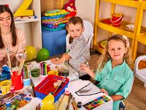 Children painting and drawing together. Craft lesson in primary school. Kids playroom organization of children painting and drawing in kid`s club. Craft lesson Royalty Free Stock Images