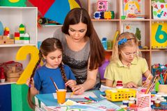 Children painting and drawing together. Craft lesson in primary school. Kids playroom organization of children painting and drawing in kid`s club. Craft lesson Stock Photography
