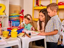 Children painting and drawing together. Craft lesson in primary school. Kids playroom organization of children painting and drawing in kid`s club. Kindergarten Royalty Free Stock Images