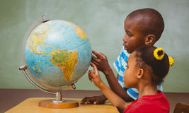 Kids pointing at globe in classroom. Side view of little kids pointing at globe in classroom Royalty Free Stock Photos