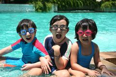 Kids in the pool. Kids with goggles in the pool on sunny day Stock Photo