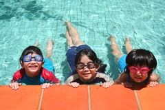 Kids in the pool. Kids with goggles in the pool on sunny day Stock Images