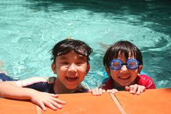 Kids in the pool. Kids with goggles in the pool on sunny day Royalty Free Stock Photos