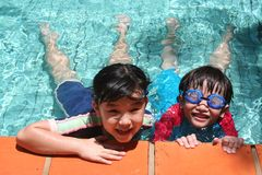 Kids in the pool. Kids with goggles in the pool on sunny day Royalty Free Stock Photo