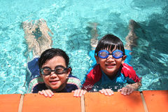 Kids in the pool. Kids with goggles in the pool on sunny day Royalty Free Stock Images