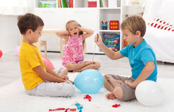 Kids popping balloons Stock Photos