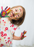 Kids portrait. Portrait of a cute cheerful happy little girl showing her hands painted in bright color stock images