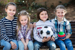 Kids posing together with ball. Happy little kids posing together with ball outdoor in city street Stock Photography