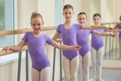 Kids practicing ballet at ballet class. Young smiling ballerina standing in pose at ballet barre royalty free stock photos