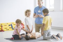 Kids practicing first aid steps. Kindergarten kids practicing first aid steps on a medical dummy with young paramedic royalty free stock image