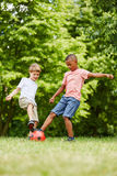 Kids practicing sport in summer. Playing soccer at the park stock photography