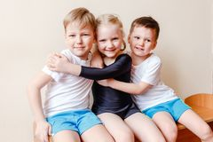 Kids pre-school children in sports uniform, girl in a black sports swimsuit. Boys in white t-shirts stock images