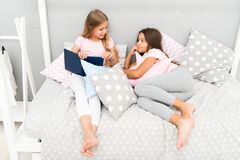 Kids prepare go to bed. Pleasant time cozy bedroom. Girls long hair cute pajamas relax read book. Satisfied with book. Happy end. Their favorite book. Girls royalty free stock photos