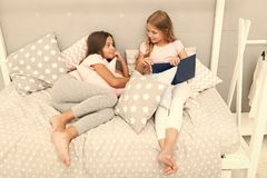 Kids prepare go to bed. Pleasant time cozy bedroom. Girls long hair cute pajamas relax read book. Satisfied with book stock photo