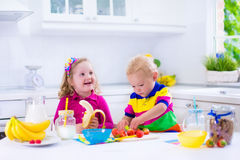 Kids preparing breakfast in a white kitchen Royalty Free Stock Photography