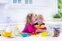 Kids preparing breakfast in a white kitchen Stock Images