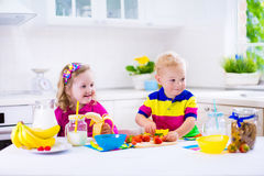Kids preparing breakfast in a white kitchen Royalty Free Stock Photos
