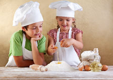 Kids preparing a cake Stock Photos