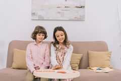Kids preparing greeting for mothers day at home. On couch royalty free stock photo