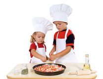 Kids preparing a pizza royalty free stock photos