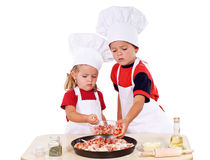 Kids preparing pizza. Two kids dressed as chefs preparing a pizza - isolated Royalty Free Stock Photo