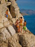 Children climbing up for a cliff dive Royalty Free Stock Photography
