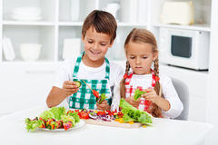 Kids preparing vegetables on a stick for a healthy snack. Young kids preparing vegetables on a stick for a healthy snack - taking their job seriously Royalty Free Stock Photos