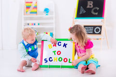 Kids at preschool painting. Kids at preschool. Two children drawing and painting at kindergarten. Boy and girl happy to go back to school. Toddler kid and baby stock photography