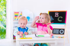 Kids at preschool painting. Kids at preschool. Two children drawing and painting at kindergarten. Boy and girl happy to go back to school. Toddler kid and baby stock image