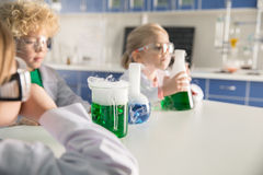 Kids in protective glasses and lab coats making experiment. In chemical laboratory stock photos