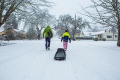 Kids pulling a sled down a snow covered suburban street. Children walk down the center of an empty street dragging sleds in the freshly fallen winter snow Royalty Free Stock Photo