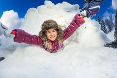 Kids are pulling smiling girl from snow cave Royalty Free Stock Images