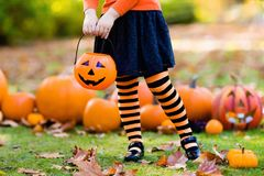 Little girl in witch costume on Halloween trick or treat. Kids with pumpkin on Halloween. Little girl in witch costume and hat playing in autumn park. Child at Royalty Free Stock Photos