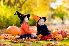 Kids with pumpkins in Halloween costumes Stock Photography