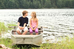 Kids in punt - first kiss. Little kids - girl and boy sitting in the punt and prepairing for the first kiss Royalty Free Stock Image