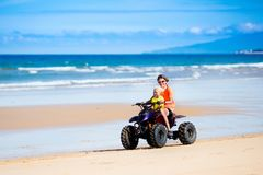 Kids on quad bike. Off road all terrain vehicle. Teenager and his little brother riding quad bike on tropical beach. Active teen age boy on quadricycle. All Stock Images