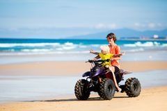 Kids on quad bike. Off road all terrain vehicle. Teenager and his little brother riding quad bike on tropical beach. Active teen age boy on quadricycle. All Royalty Free Stock Photos