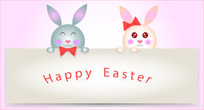 Kids rabbits greeting sign. A pair of rabbits holding a sign with a wish Happy Easter Royalty Free Stock Photo