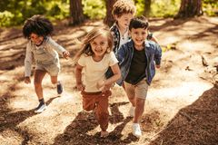 Kids race in the forest. Group of four kids running together in the forest. Children having a race to climb up hill forest path royalty free stock photography
