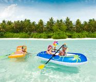 Kids in a raft. A trio of kids playing in a raft at the beach Royalty Free Stock Images