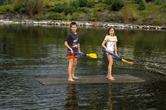 Kids on raft holding paddles Stock Image