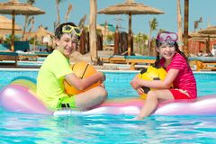 Kids on raft in pool. A young boy and girl riding a raft in a swimming pool Royalty Free Stock Photo