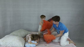 Kids rage on inflatable bed. They throw pillows and jump stock video footage