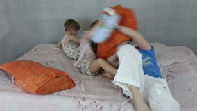 Kids rage on inflatable bed. They throw pillows and jump stock footage